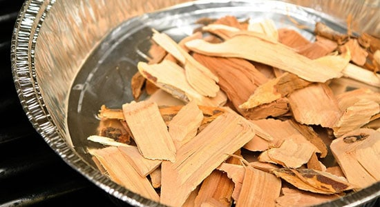Move the chips of wood that you chose from the water bowl to the smokehouse